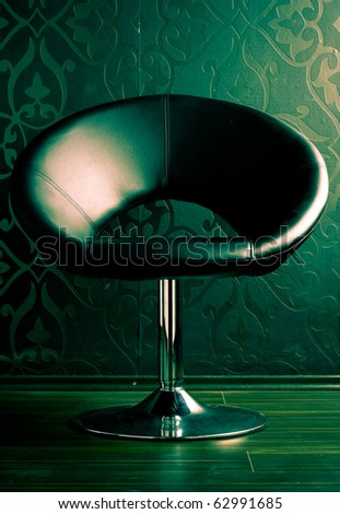 Leather chair against a wallpapered wall - stock photo