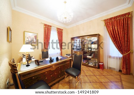 Leather chairs and gilt table with lamp in home office in classic style. - stock photo
