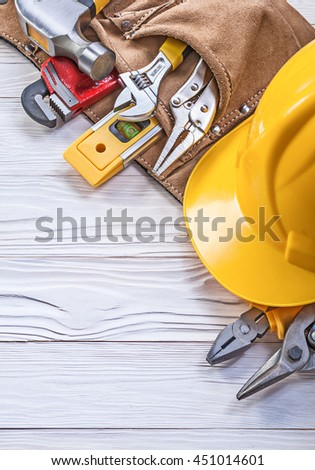 Leather construction belt hard hat on wooden board maintenance concept.