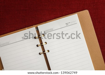Leather cover notebook on fabric background - stock photo