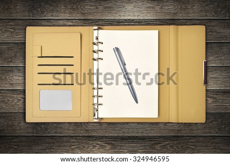 leather cover notebook with pen on desk top - stock photo