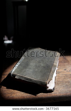 Leather covered old bible lying on a wooden table in a beam of sunlight (not an isolated image) Shallow Depth of field – Focus on closest edge of bible - stock photo