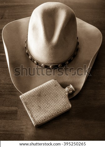 Leather cowboy hat, studded hat band and flask - stock photo