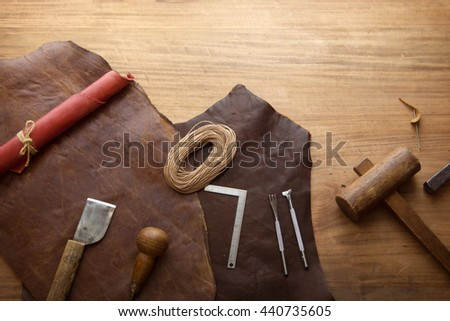 Leather craft. Leathersmith's work desk . Pieces of hide and leather working tools on a work table. Top view.