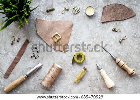 Leather craft. Tanner's tools on grey stone background top view copyspace