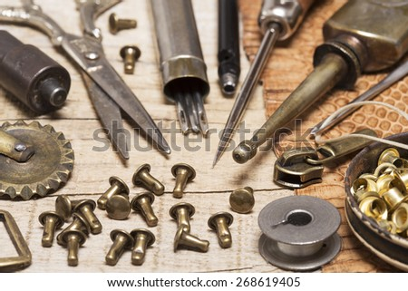 Leather craft tools, buckles and a snake skin  - stock photo