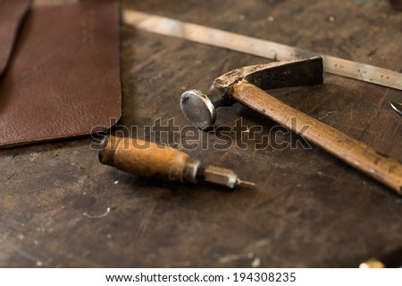 Leather crafting tools on working desk - stock photo