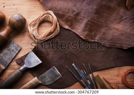 Leather craftmans work desk . Piece of hide and working tools on a work table. - stock photo