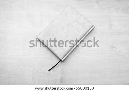 Leather diary book laying on wooden table in - stock photo