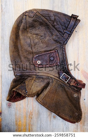 leather dirty vintage helmet over wooden background - stock photo