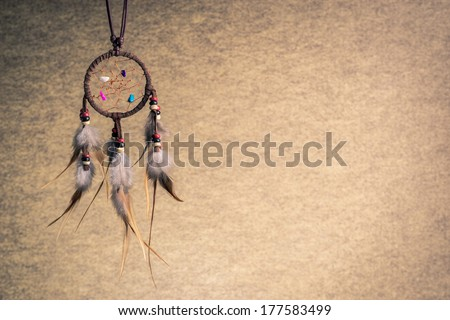 Leather dream catcher on sepia tone background, left copy space - stock photo