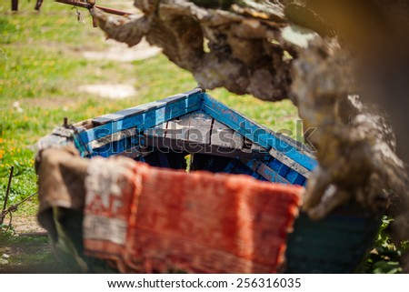 Leather drying in the sun, laid on a blue broken boat - stock photo