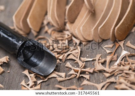 leather edge trimming tool with scraps on wood - stock photo
