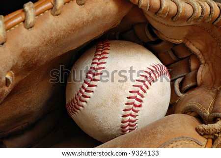 Leather glove with baseball.  Close-up with shallow dof.  Focus on seams of ball.