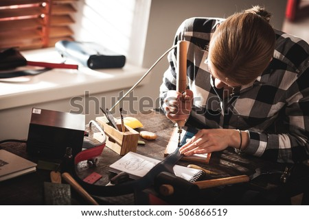 Leather handbag craftsman at work in a workshop