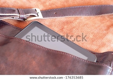 Leather handbag with tablet inside - stock photo