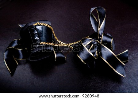 Leather handcuffs with golden chains on dar background - stock photo