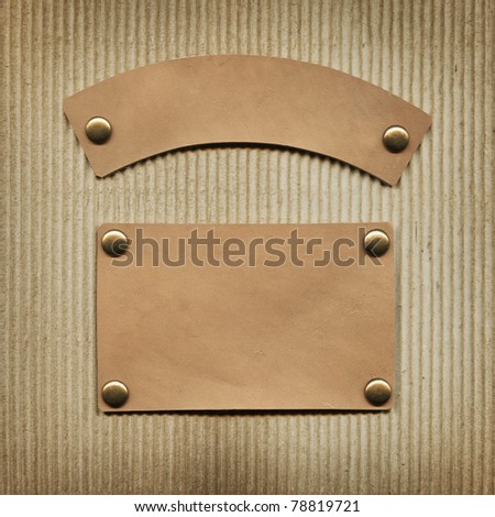 Leather label on corrugated board - stock photo