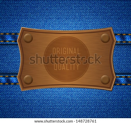 Leather label with rivets on the jeans with seams - stock photo