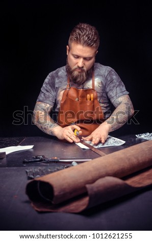 Leather man creating leatherwork
