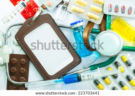 Leather name Tag with Medical frame of Stethoscope pill ampules and syringe isolated on white background