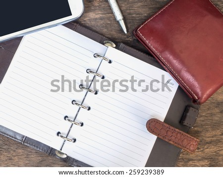 leather personal organizer, mobile phone, purse and pen on wood desk - stock photo