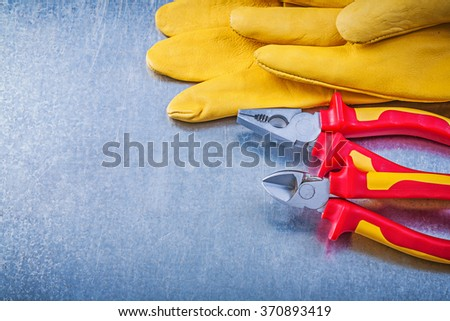 Leather safety gloves pliers wire-cutter on metallic background electricity concept. - stock photo