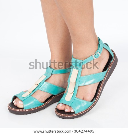 leather sandals blue with gold applied to the foot of the women's  on white background - stock photo