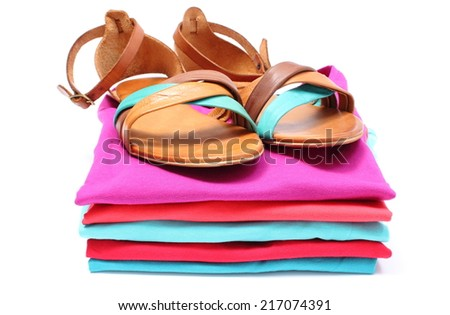 Leather sandals lying on pile of colorful shirts. Isolated on white background - stock photo