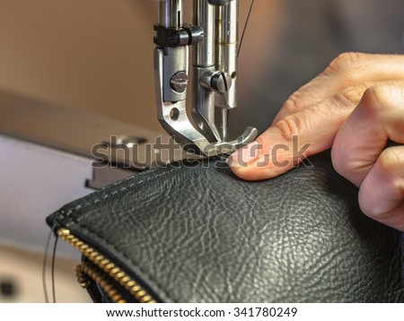 Leather sewing machine in action in a workshop with hands working on a shoulder bag - stock photo