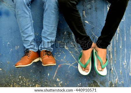 leather shoes and flip-flops with jeans on concrete wall - stock photo