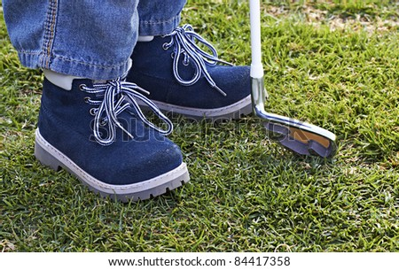 leather shoes of a small boy on the golf course with golf club. - stock photo