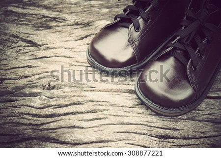 leather shoes on wooden table with vintage tone - stock photo