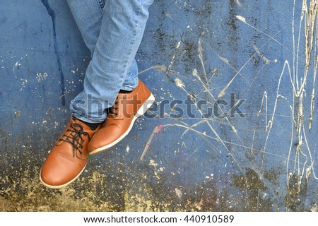 leather shoes with jeans on concrete wall - stock photo