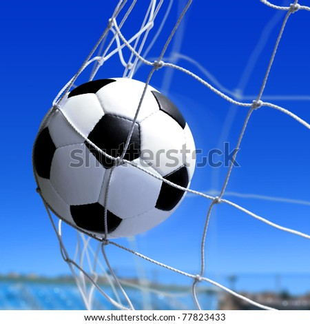 leather soccer ball flies into the net gate - stock photo