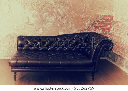 Leather sofa in the English style in the room with old vintage red brick walls