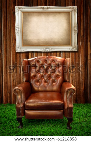 Leather sofa on green grass and photo frame against wooden wall
