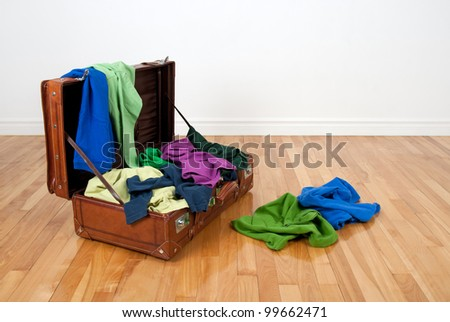 Leather suitcase on a wooden floor in an empty room, full of colorful clothing. - stock photo