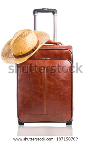 Leather suitcase with hat on it isolated against a white background. Travel concept - stock photo