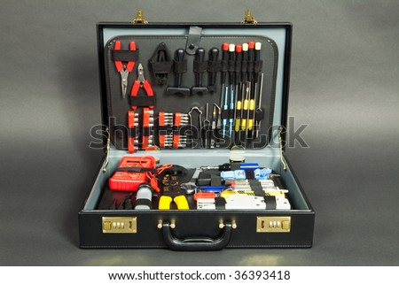 Leather suitcase with tools against a dark background