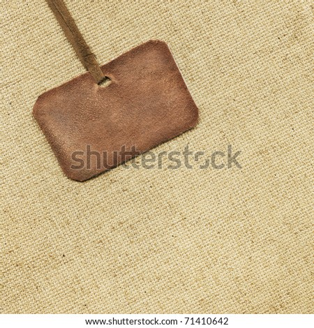Leather tag on the background of fabric - stock photo