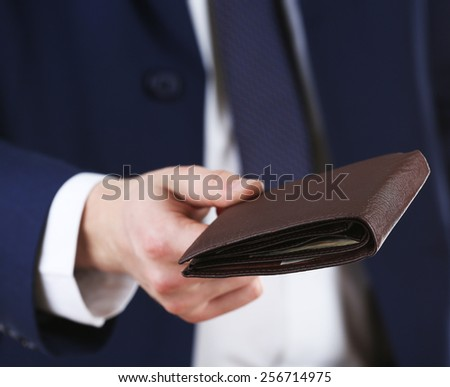 Leather wallet with money in male hands on white background - stock photo