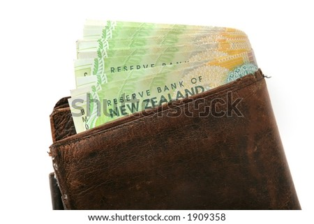 Leather wallet with wad of $20 New Zealand bills hanging out of it. - stock photo