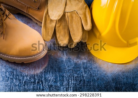 Leather working lace boots protective gloves and hard hat on scratched metallic background construction concept. - stock photo