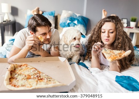 Leave something for me. Couple and their dog enjoying pizza in bed. Selective focus, depth of field  - stock photo