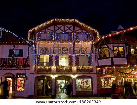 LEAVENWORTH, WA/USA - DECEMBER 21, 2013: This illustrative editorial a Bavarian store lit up with Christmas lights at night with shoppers. - stock photo