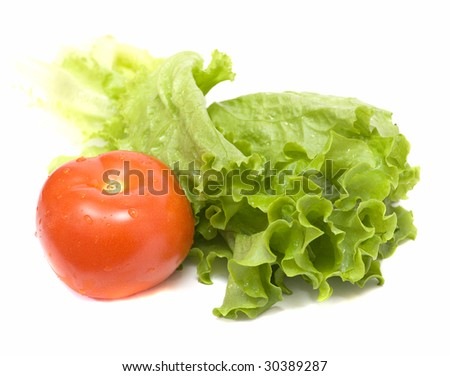 Leaves of green salad with red tomato isolated - stock photo