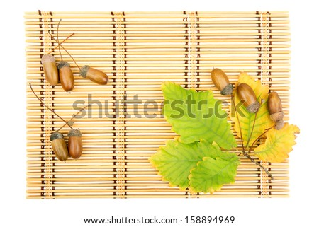 leaves of oak acorns on a mat from straw - stock photo