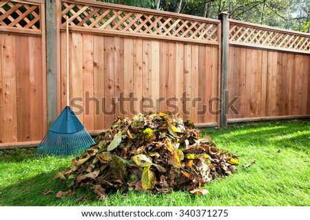 Leaves raked into a pile in a backyard beside a wooden fence. - stock photo
