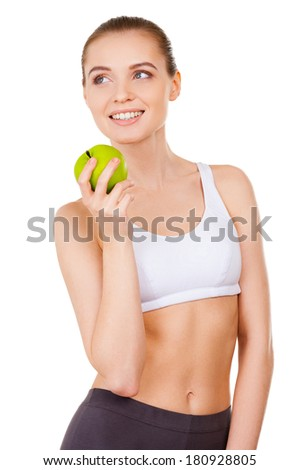 Leaving a healthy life. Beautiful young woman in sports clothing holding a green apple and smiling while standing isolated on white - stock photo